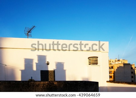 Roof ventilation silhouette shadows on white stone wall and antenna against blue sky in Mallorca, Spain. - stock photo