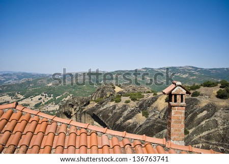 Roof with chimney against mountain landscape in Greece - stock photo