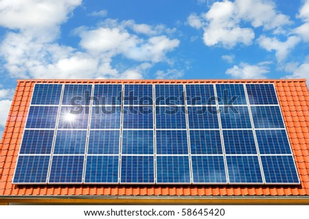Roof with solar panel reflecting the sun, in the background a perfect sky with fluffy white clouds - stock photo