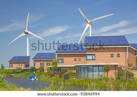 Roof with solar panels and wind turbines in the background - stock photo