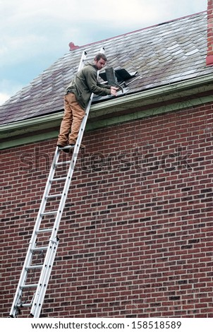 Roof Worker on Ladder - stock photo