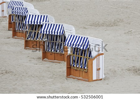 Roofed beach chairs placed in a line can be seen on the Baltic beach at the seashore in Kolobrzeg in Poland