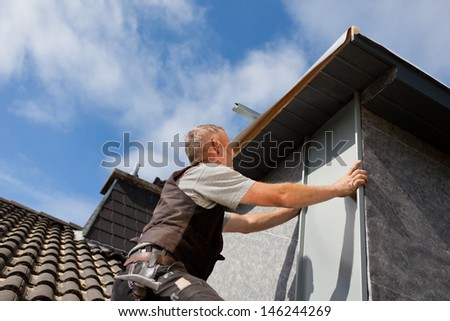 Roofer assembles a metal piece into the dormer wall on a sunny day - stock photo
