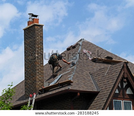 roofer at work repairing a steeply sloped shingle roof  - stock photo