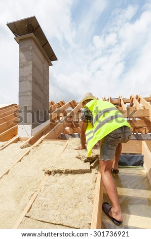 Roofer builder worker installing roof insulation material. New house under construction with chimney - stock photo