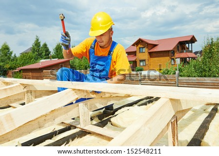 roofer carpenter worker nailing wood board with hammer on roof installation work - stock photo