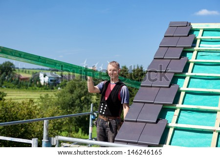 Roofer carrying a wooden beam to construct the roof structure - stock photo