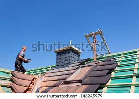 Roofer carrying gray tiles across the roof