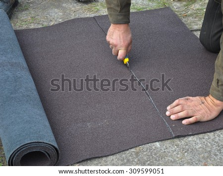 Roofer cutting roll roofing felt or bitumen during waterproofing works. Roofing repair. - stock photo
