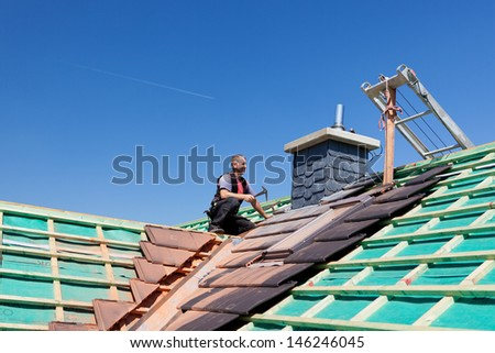 Roofer hammering nails on the beams on top of an unfinished roof - stock photo