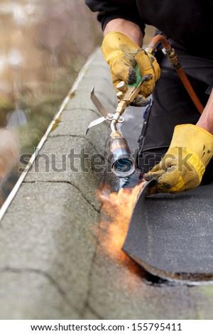 Roofer installing roofing felt - stock photo