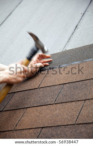 roofer made a roof with slates hammer in hand - stock photo