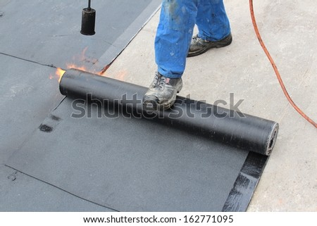 Roofer on a flat roof - stock photo