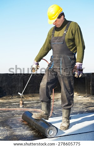 Roofer preparing part of bitumen roofing felt roll for melting by gas heater torch flame - stock photo