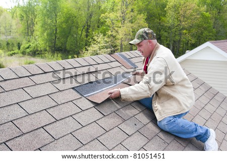 Roofer repairing damaged shingles after a storm with very high winds came through over night - stock photo