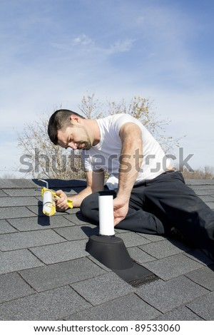 Roofer repairing leaks around vent pipes on house roof, water came in and damaged ceiling during strong rain storms - stock photo