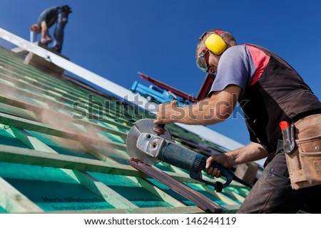 Roofer using a hand circular saw to cut a roof-tile - stock photo