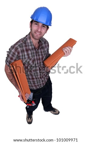 Roofer with canal tiles - stock photo