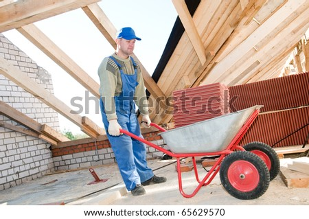 Roofer worker distibuting red clay tiling in wheel barrow at roof - stock photo