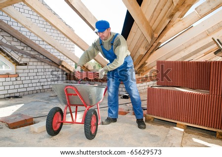 Roofer worker loading red clay tiling into wheel barrow for distribution - stock photo