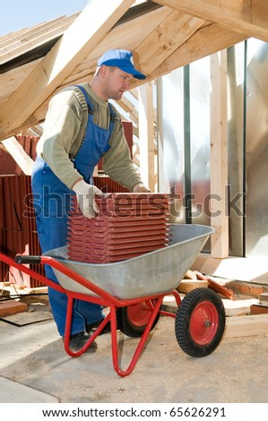 Roofer worker working with red clay tiling and wheel barrow - stock photo