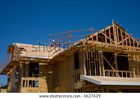 Roofer works on top of new two-story house - stock photo