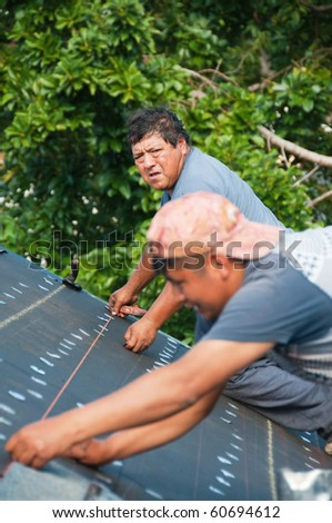 Roofers installing shingles on roof using chalk lines for correct installation - stock photo