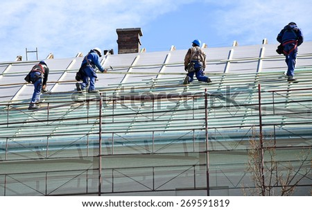Roofers on the roof - stock photo