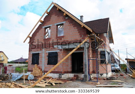 Roofing Construction and Building New  Ceramic Bricks House with Modular Chimney, Skylights, Attic, Facade and Eaves Exterior. Install, Repair Asphalt Shingles or Bitumen Tiles on the Rooftop Outdoor. - stock photo