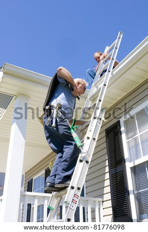 Roofing contractor repairing damaged roof on home after recent wind storms, many roofs were damaged - stock photo