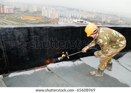 Roofing felt installation with heating and melting roll of bitumen roll by torch on flame - stock photo