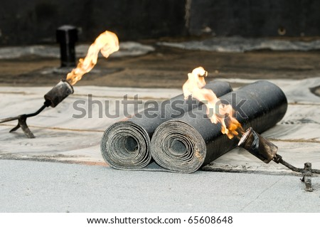 roofing felt roll and one torch blowpipes with open flame - stock photo