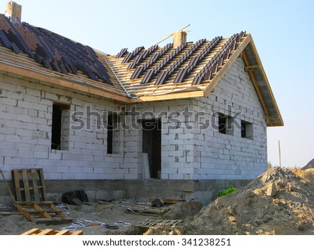 Roofing House Exterior. A roof under construction site with stacks of roof tiles ready to fasten outdoor. - stock photo