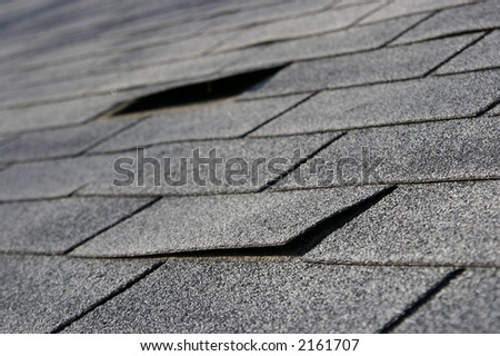 Roofing trouble - damage to shingles that needs repair - home maintenance series. Narrow DOF - stock photo