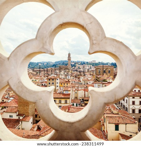 roofs, red tiles and narrow streets through the fence ornament bell tower in Florence, Italy - stock photo