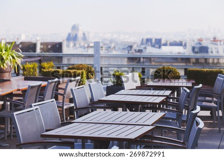 rooftop cafe, open terrace with wooden tables - stock photo