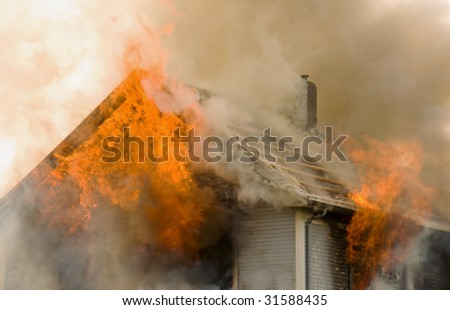 Rooftop house on fire - stock photo