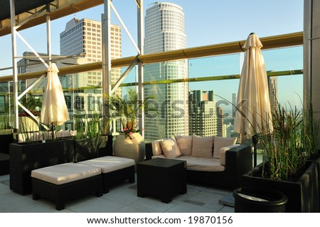 Rooftop seating area with a skyscraper sunset view
