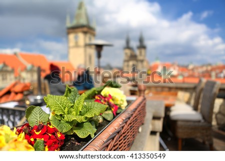 Rooftop terrace overlooking Prague Czech Republic capital city with Orloj and Church of Our Lady before Tyn with planted flowers on a beautiful sunny blue sky day - stock photo