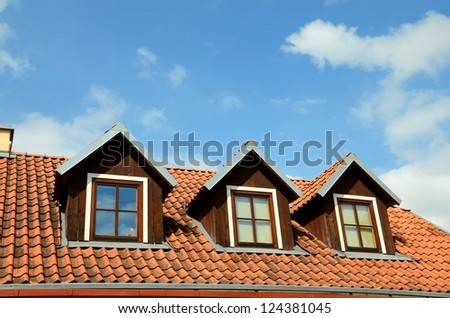 Rooftop with windows against blue sky with clouds - stock photo
