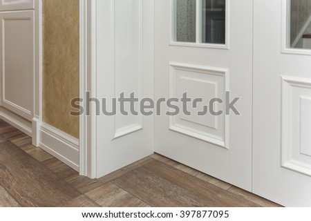 Room corner, white door with glass, a wooden floor, a white wall.