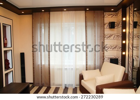 Room design in yellow and brown tones with armchair curtains and lighting. Interior design of residential apartments