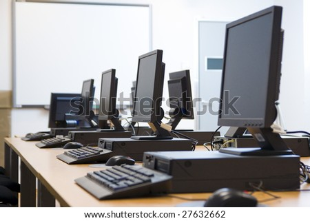 Room equipped with black computers and chairs. - stock photo