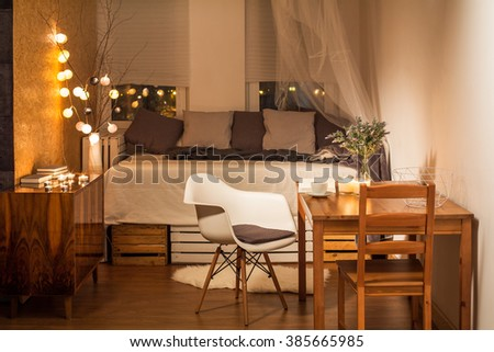 Room in brown and beige with bed, chair and table