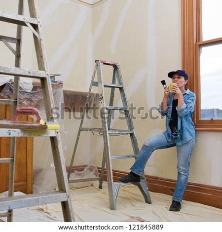 Room in house with patched walls ready for painting with female renovator have a cup of tea - stock photo