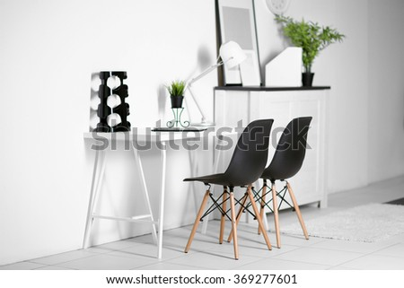 Room interior with commode, frames, chairs and table on white wall background - stock photo