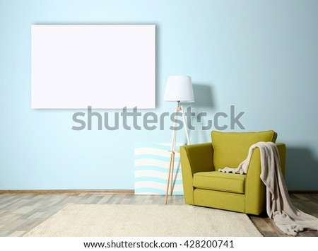 Room interior with green armchair and empty picture frame on blue wall background - stock photo