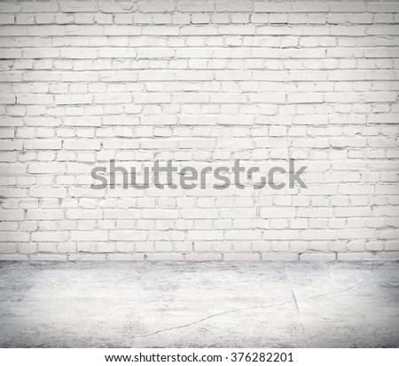 Room interior with white brick wall and concrete floor - stock photo