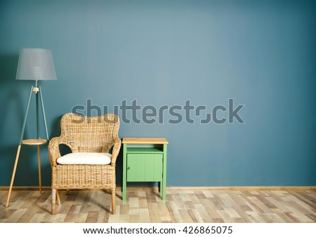 Room interior with wicker chair on dark grey wall background - stock photo