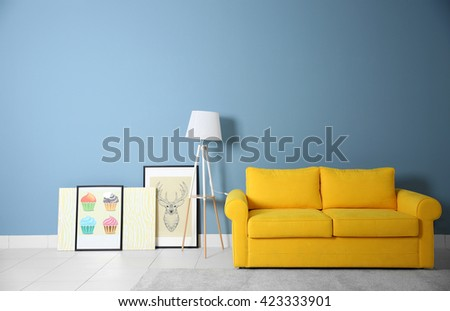 Room interior with yellow sofa on blue wall background - stock photo
